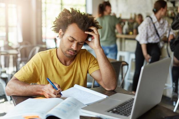 Estudante universitário inteligente em roupas casuais, olhando atentamente em seu caderno escrevendo notas usando o computador laptop, sendo focado em sua escrita sentado no café. homem que trabalha duro estando ocupado Foto gratuita