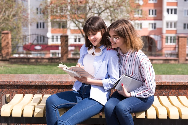 Estudantes adolescentes, sentar-se banco, com, livros abertos Foto gratuita