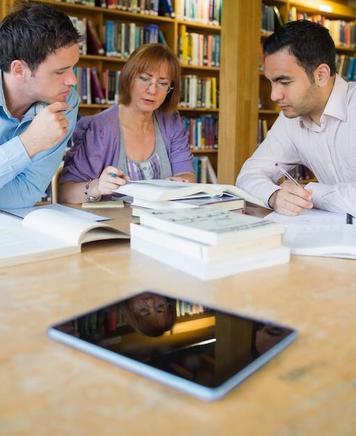 Estudantes adultos estudando juntos na biblioteca Foto Premium