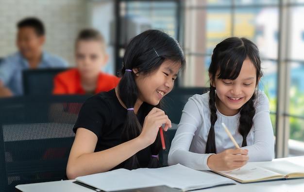 Estudantes asiáticos se divertem escrevendo no caderno em sala de aula Foto Premium