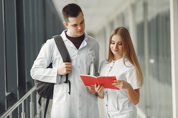 Estudantes de medicina estão lendo um livro em um hospital Foto gratuita