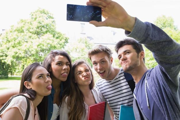 Estudantes felizes tomando uma selfie fora do campus Foto Premium