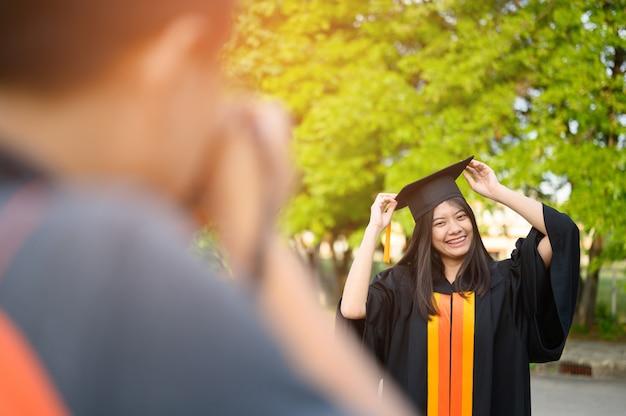 Estudantes fêmeas de cabelos compridos que vestem o plissado preto vestem a expressão da alegria na graduação na universidade. Foto Premium
