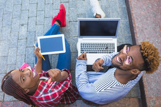 Estudantes negros posando com gadgets Foto gratuita