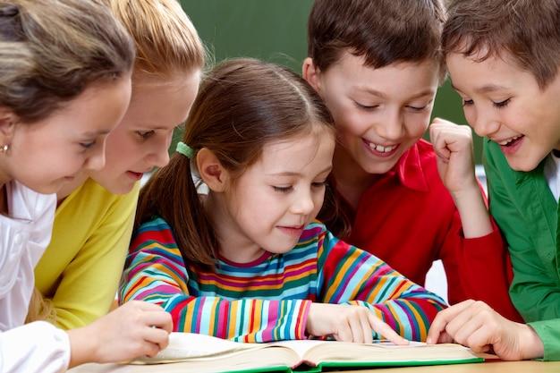 Estudantes que têm um bom tempo durante a leitura em sala de aula Foto gratuita