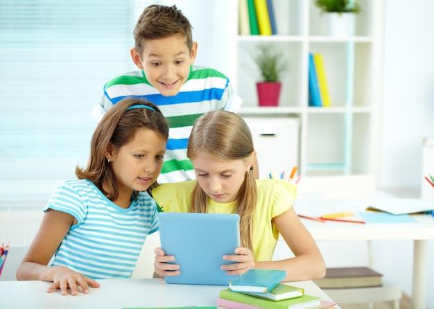 Estudantes que usam uma tabuleta digital na sala de aula Foto gratuita