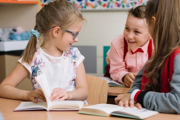 Estudantes sentados em sala de aula conversando Foto gratuita