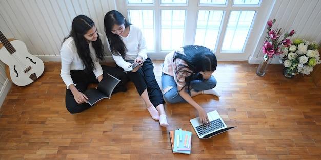 Estudantes universitários estão relaxando com um laptop e tablet na sala de estar. Foto Premium