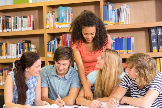 Estudantes universitários, fazendo, dever casa, em, biblioteca Foto Premium
