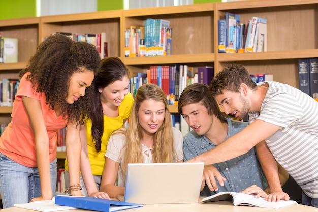 Estudantes universitários, usando computador portátil, em, biblioteca Foto Premium