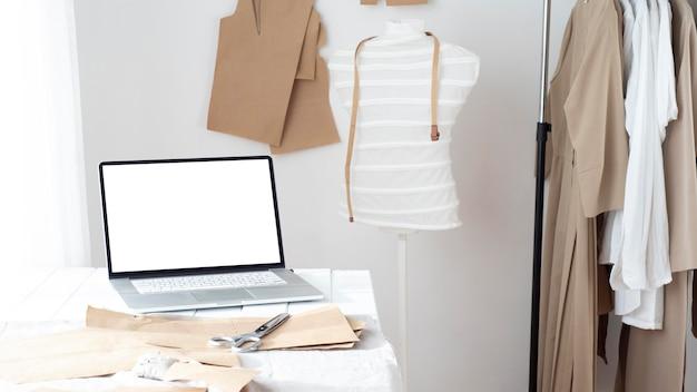 Estúdio de costura com forma de vestido e laptop Foto gratuita