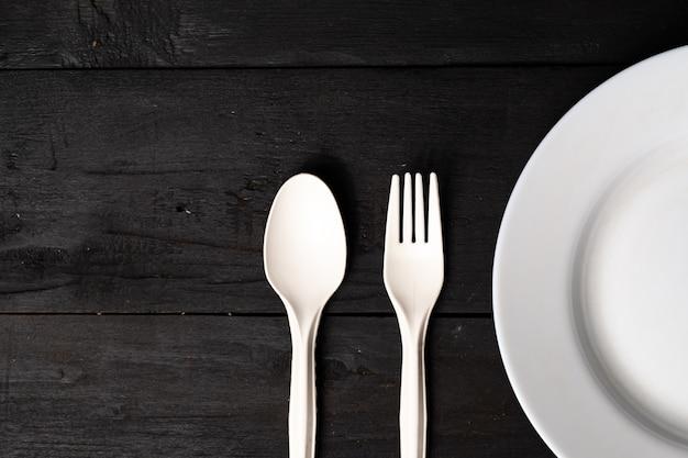 Esvazie a bacia, a forquilha e a colher brancas na tabela de madeira preta, opinião do close-up. conceito de dieta: configuração plana de pratos de cozinha limpa na superfície rústica escura Foto Premium