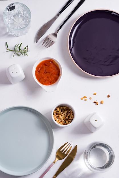 Esvazie em volta dos pratos azuis e roxos com talheres, amendoins torrados e molho de tomate. vista superior com espaço de cópia para você projetar. Foto Premium