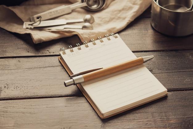 Esvazie o caderno do espaço branco com as ferramentas da padaria da pena e da pastelaria no fundo de madeira. Foto Premium