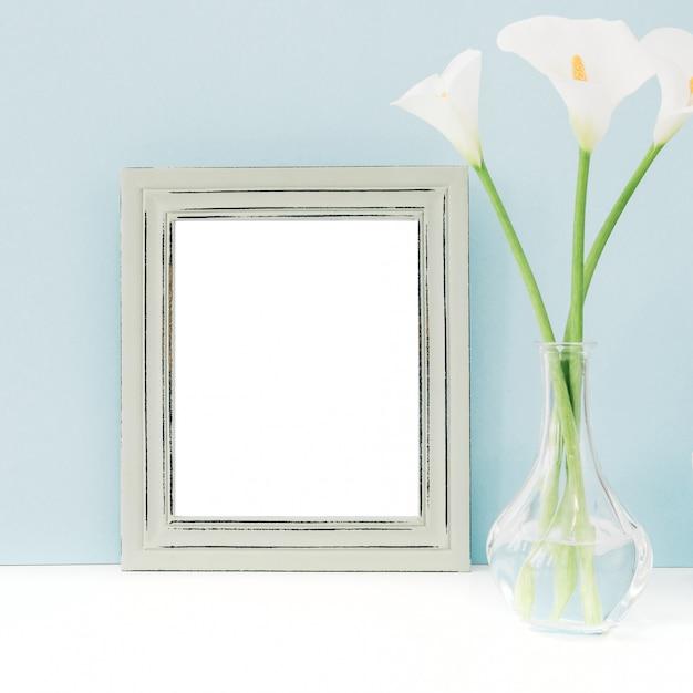 Esvazie o quadro de madeira e as flores no vaso na tabela no azul. brincar Foto Premium