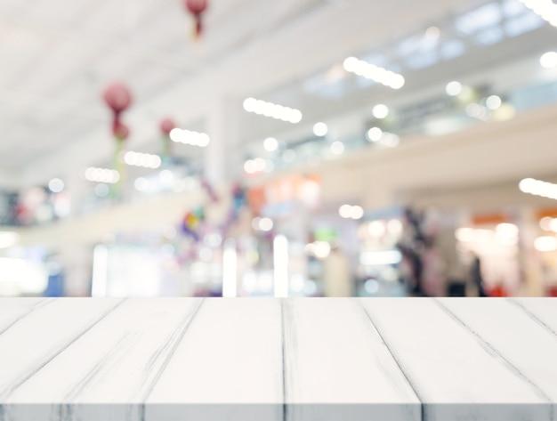 Esvazie o tampo da mesa branca e desfocar o centro comercial em segundo plano Foto gratuita