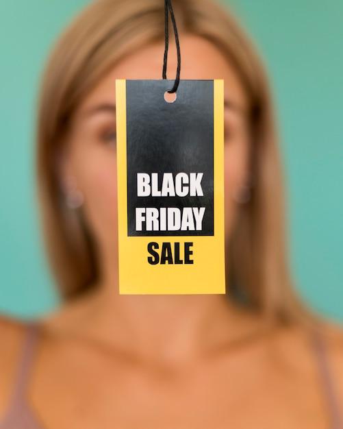 Etiqueta de venda de sexta-feira negra em mãos de mulher desfocada Foto gratuita
