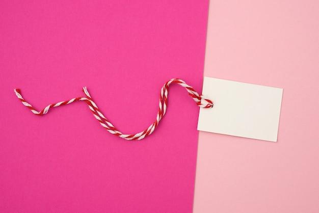 Etiqueta retangular de papel branco em uma corda em um fundo colorido Foto Premium