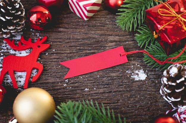 Etiqueta vermelha em branco com decorações de natal na mesa de madeira. Foto Premium