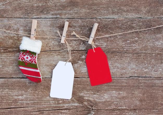 Etiquetas de papel branco e vermelho e meias de natal penduradas em uma corda com prendedores de roupa Foto Premium