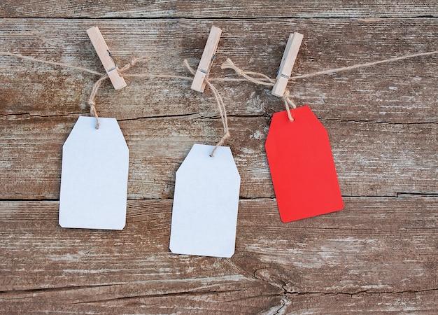 Etiquetas de papel branco e vermelho em branco presas com prendedores de roupa de madeira à corda Foto Premium