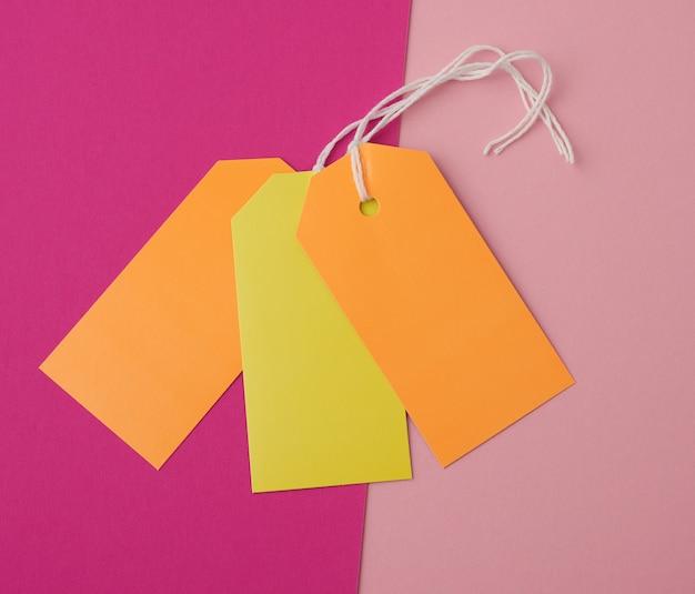 Etiquetas retangulares de papel em uma corda em um fundo colorido Foto Premium