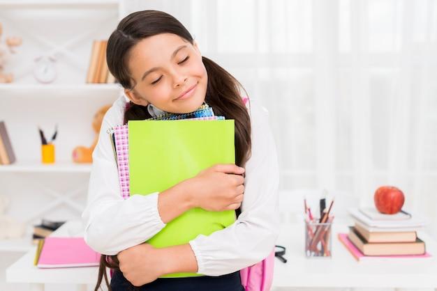 Étnica colegial fechando os olhos abraçando cadernos Foto gratuita