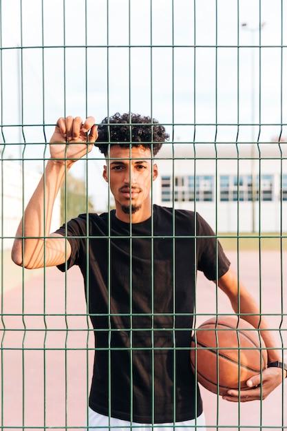 Étnica jovem macho com basquete por trás da cerca Foto gratuita