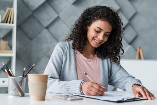 Étnica mulher trabalhando no balcão no escritório Foto gratuita