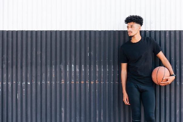Étnico homem com basquete a desviar o olhar Foto gratuita