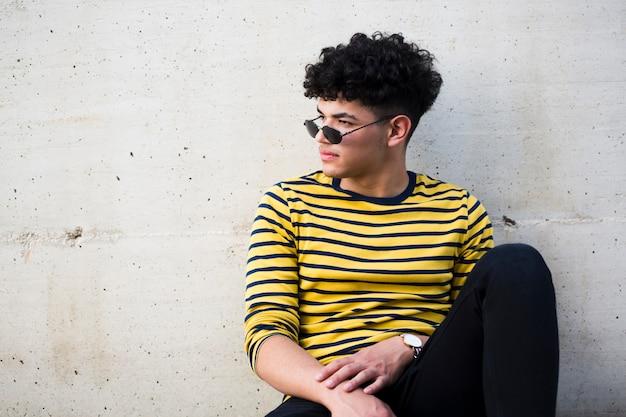 Étnico jovem elegante na camisa listrada brilhante e óculos de sol Foto gratuita