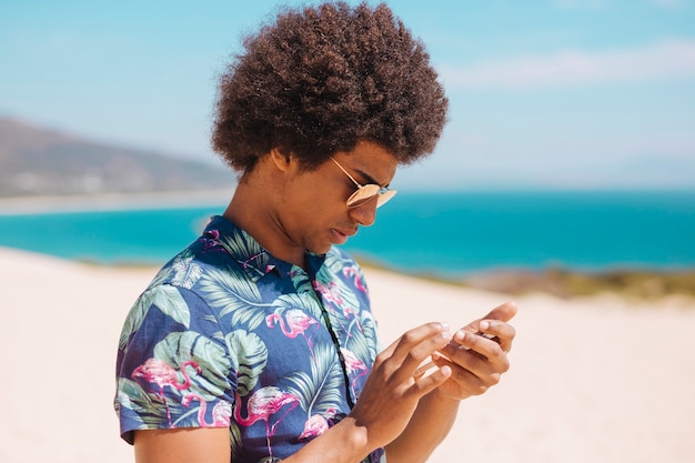 Étnico masculino olhando para smartphone na praia Foto gratuita