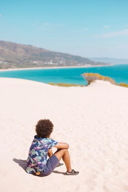 Étnico masculino sentado na areia da praia Foto gratuita