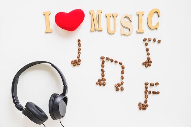 Eu amo música texto com grãos de café torrados musicais e fone de ouvido no fundo branco Foto gratuita