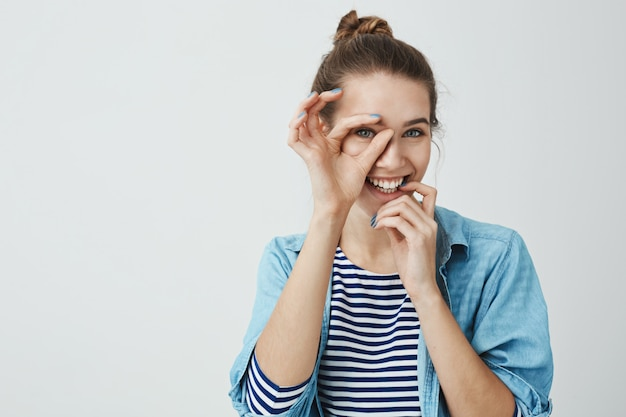 Eu estou apontando para você. retrato de brincalhão feliz namorada bonita com penteado coque segurando bem sinal sobre o olho e olhando pensei nisso, tocando o lábio com a mão e sorrindo amplamente Foto gratuita