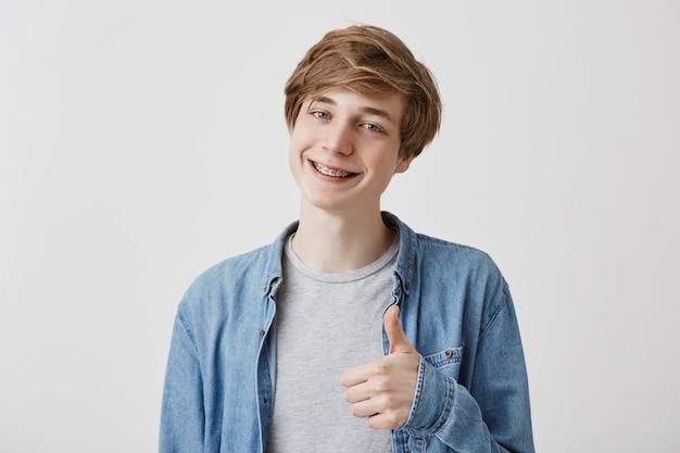 Eu gosto disso. bom trabalho. feliz jovem loiro vestindo camisa jeans, fazendo os polegares para cima o sinal e sorrindo alegremente com aparelho, mostrando seu apoio e respeito a alguém. linguagem corporal Foto gratuita