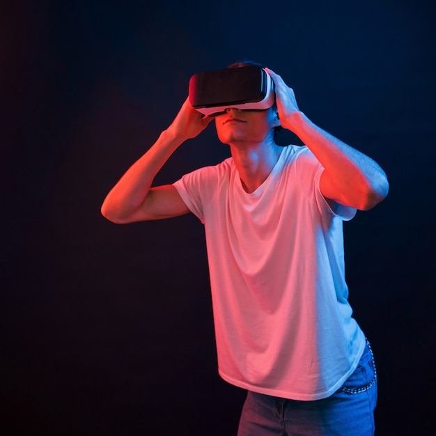 Eu não posso acreditar nos meus olhos. jovem usando óculos de realidade virtual em um quarto escuro com iluminação neon Foto Premium