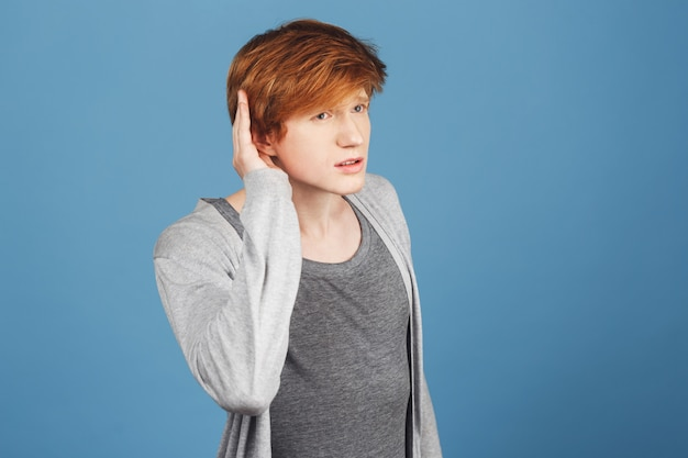Eu não te ouço. copie o espaço. close-up de cara bonito sério com cabelo vermelho em roupas casuais, segurando a mão perto da orelha, tentando ouvir o que seu amigo está dizendo no café barulhento Foto gratuita