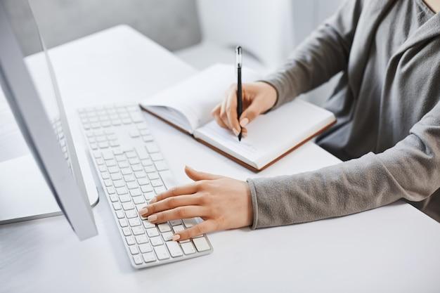 Eu posso lidar com várias tarefas. cortada tiro bem sucedida garota digitando no teclado e fazendo anotações enquanto olha para a tela do computador e estuda novos gráficos de negócios. não há tempo para descansar Foto gratuita