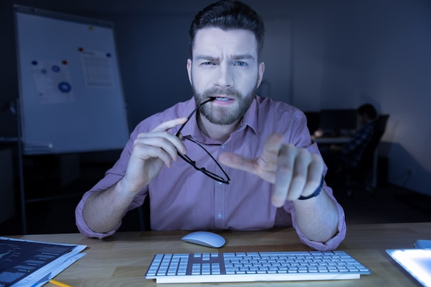 Eu preciso descansar. bom homem nervoso e cansado de ti segurando seus óculos e mordendo-os enquanto olha para a tela do computador Foto Premium