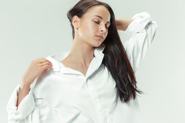 Eu sou jovem e bonita retrato de uma linda garota de cabelos escuros em estúdio cinza Foto gratuita