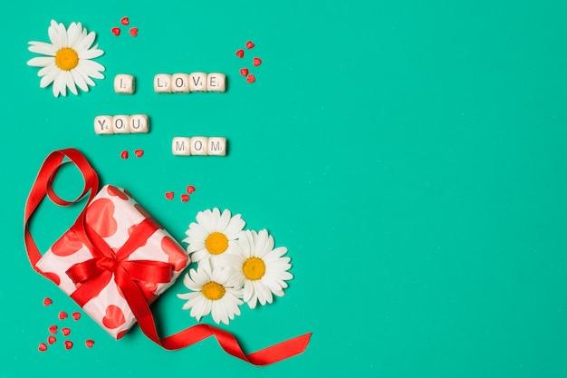 Eu te amo mãe título perto de flores brancas e caixa de presente Foto gratuita