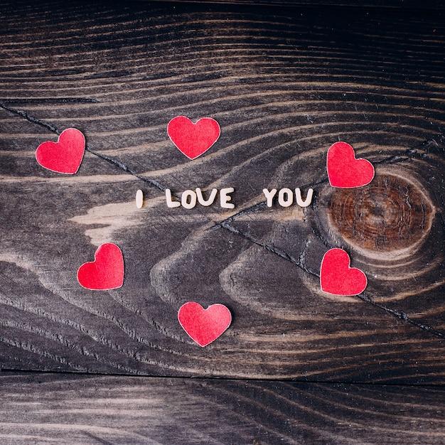 Eu te amo mensagem escrita em letras de macarrão e corações de papel Foto Premium