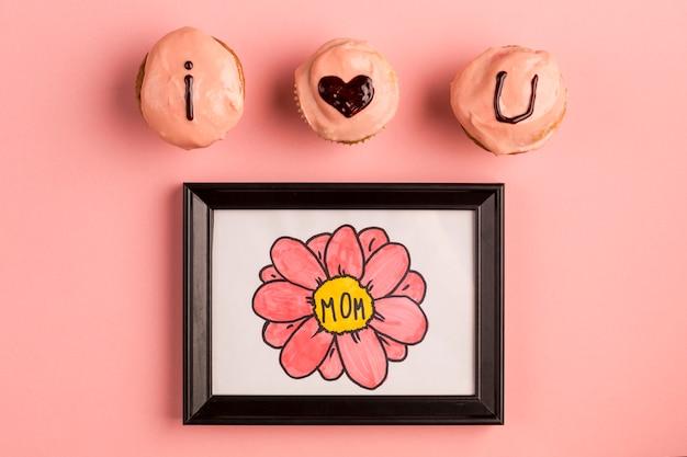 Eu te amo título em bolinhos saborosos perto de moldura de foto Foto gratuita