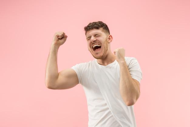 Eu venci. homem feliz de sucesso vencedor comemorando ser um vencedor. imagem dinâmica do modelo masculino caucasiano no fundo rosa do estúdio. Foto gratuita
