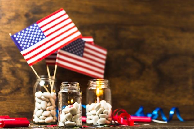Eua bandeira americana e velas acesas no branco doces jarra na mesa de madeira Foto gratuita