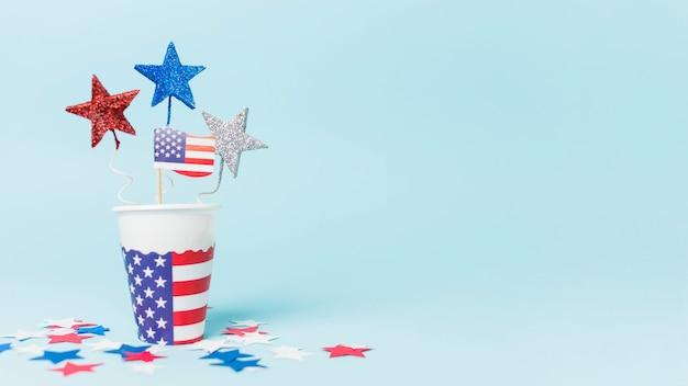 Eua bandeira e estrela adereços no copo descartável contra o fundo azul Foto gratuita
