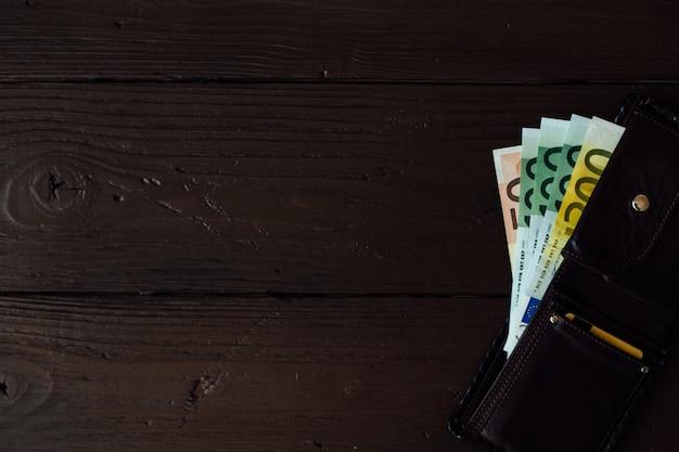 Euro dinheiro na carteira marrom no fundo de madeira Foto gratuita