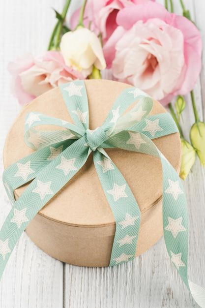 Eustoma flor e caixa de presente com fita verde estrela Foto Premium