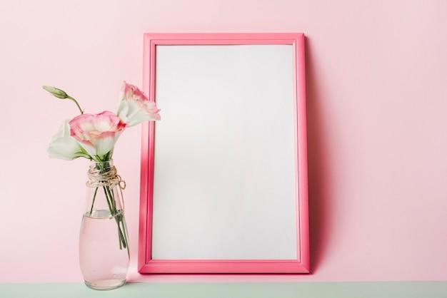 Eustoma flores no vaso perto da moldura branca em branco com borda contra fundo rosa Foto gratuita